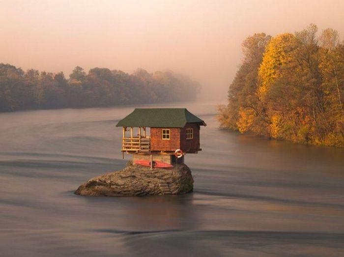 tiny house casa pequena construida roca rio arboles