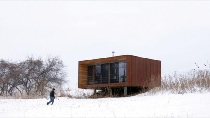 tiny house casa pequena construida ventanal arboles nieve persona