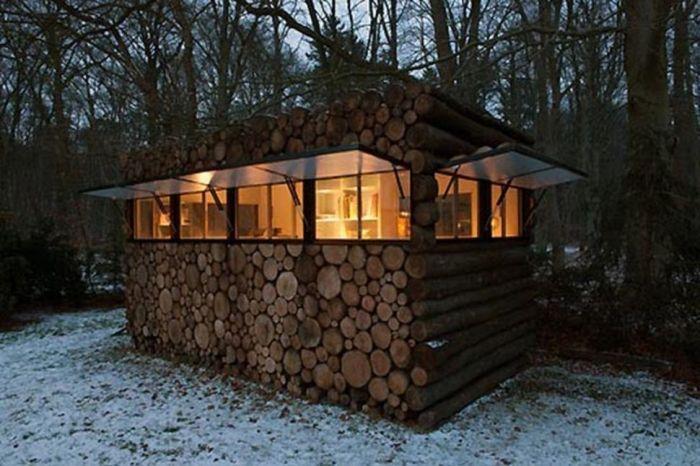 tiny house casa pequena construida troncos ventanales luz noche naturaleza nieve