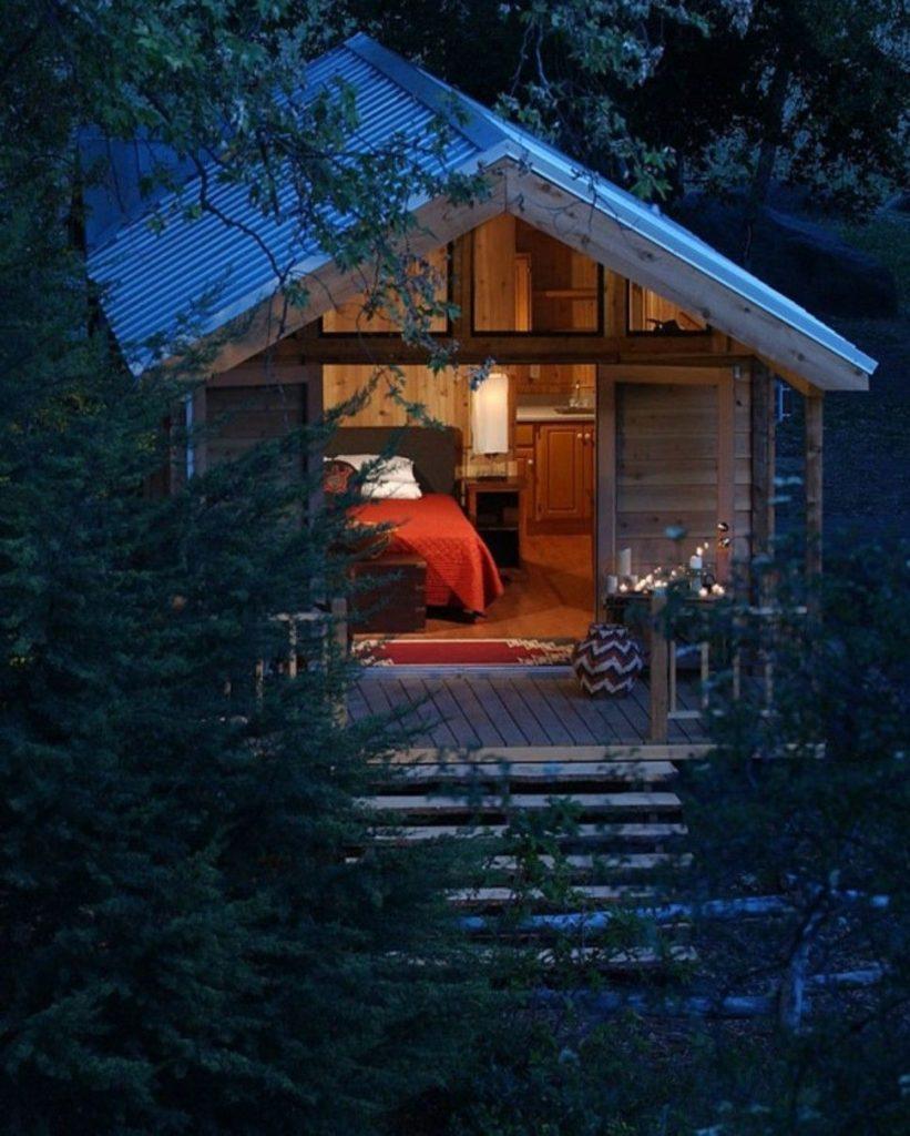 tiny house casa pequena construida madera tejado metalico naturaleza noche luz escalera