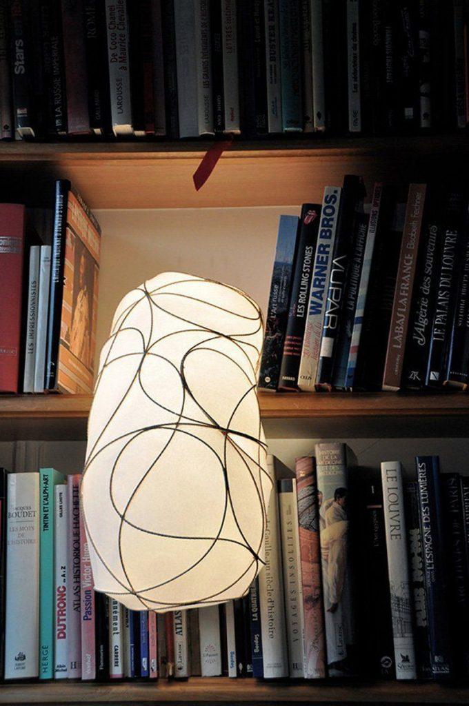 detalle lampara L encendida entre libros