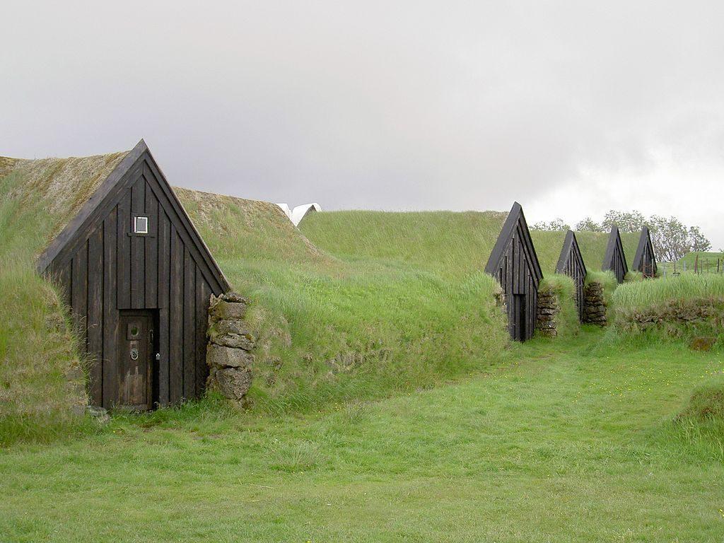 tipos-casas-mundo-bajo-tierra-fachada-madera-prado-verde-cielo-gris