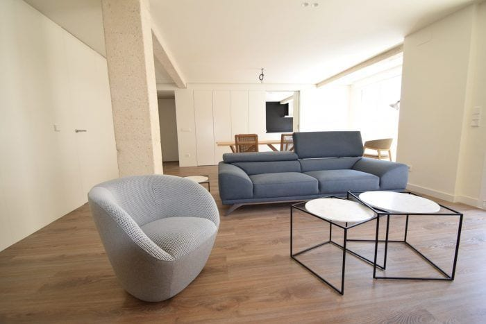 Piso reformado interior suelo madera sofa butaca mesita