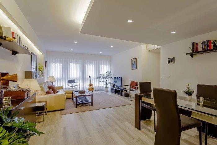 reforma piso salon  mesa sofa estanterias ventanal luz